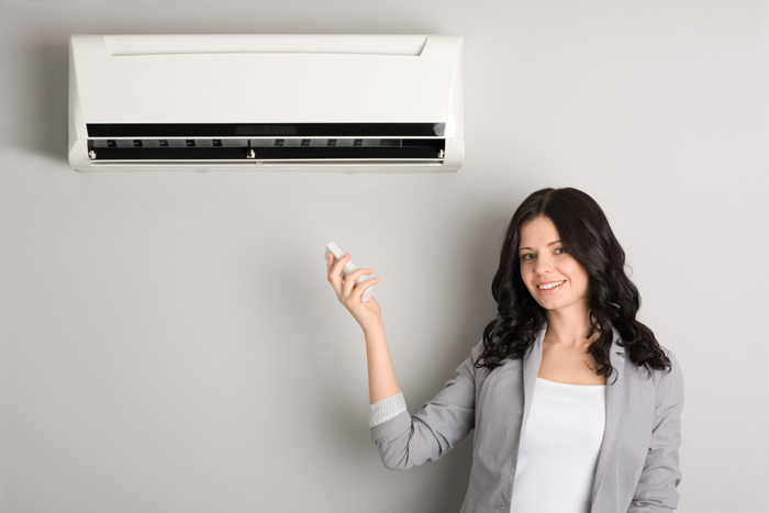 girl pointing a remote control at a heat pump