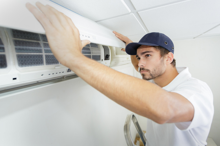 tech guy carefully installing new ac