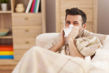 Man blowing his nose while lying sick in bed
