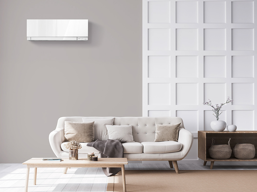 MITSUBISHI HEAT PUMPS SOLD AND INSTALLED BY HEAT AND COOL - HEAT PUMP IN A GREY LIVING ROOM, ABOVE A GREY SOFA